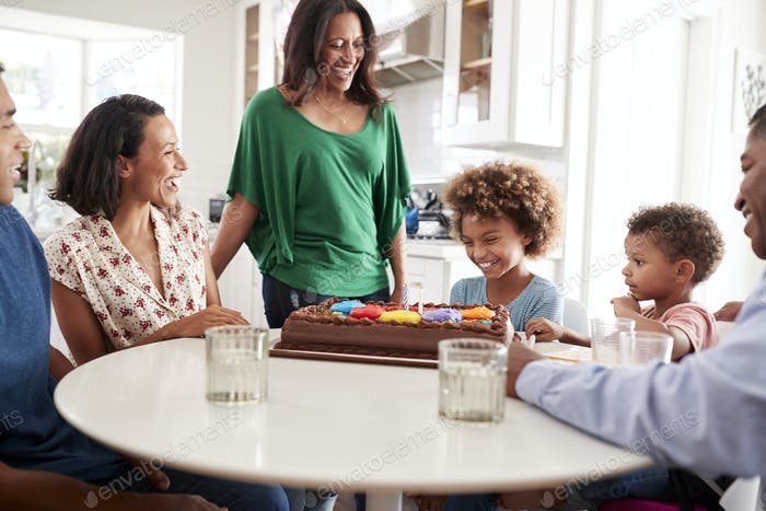 Family gathered around the kitchen table celebrating the pre-teen daughter's birthday