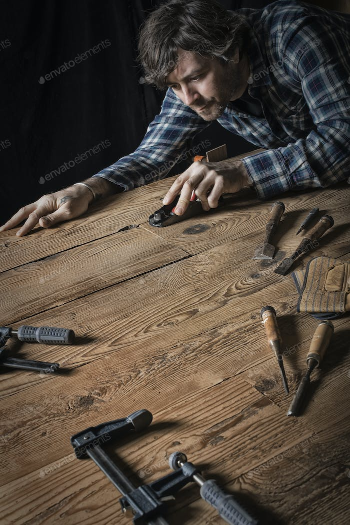 A man working in a reclaimed lumber yard workshop sanding an uneven piece of wood.
