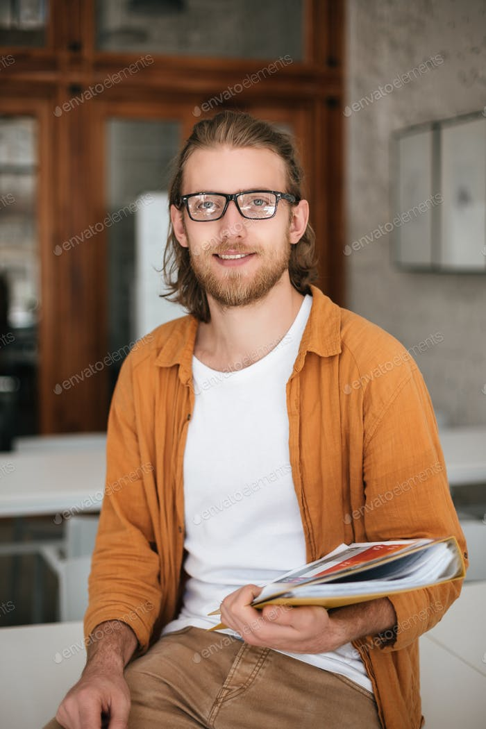 Nice boy with blond hair and beard in glasses looking in camera while holding magazines in hands