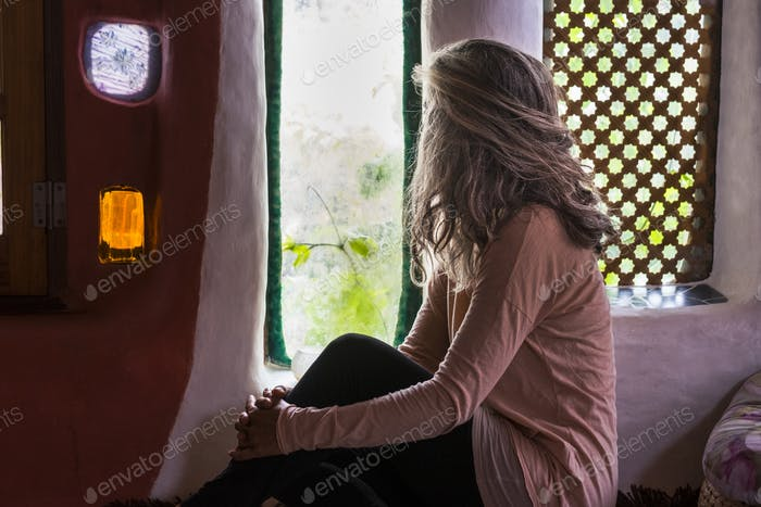 Lonely caucasian woman at home look through the window