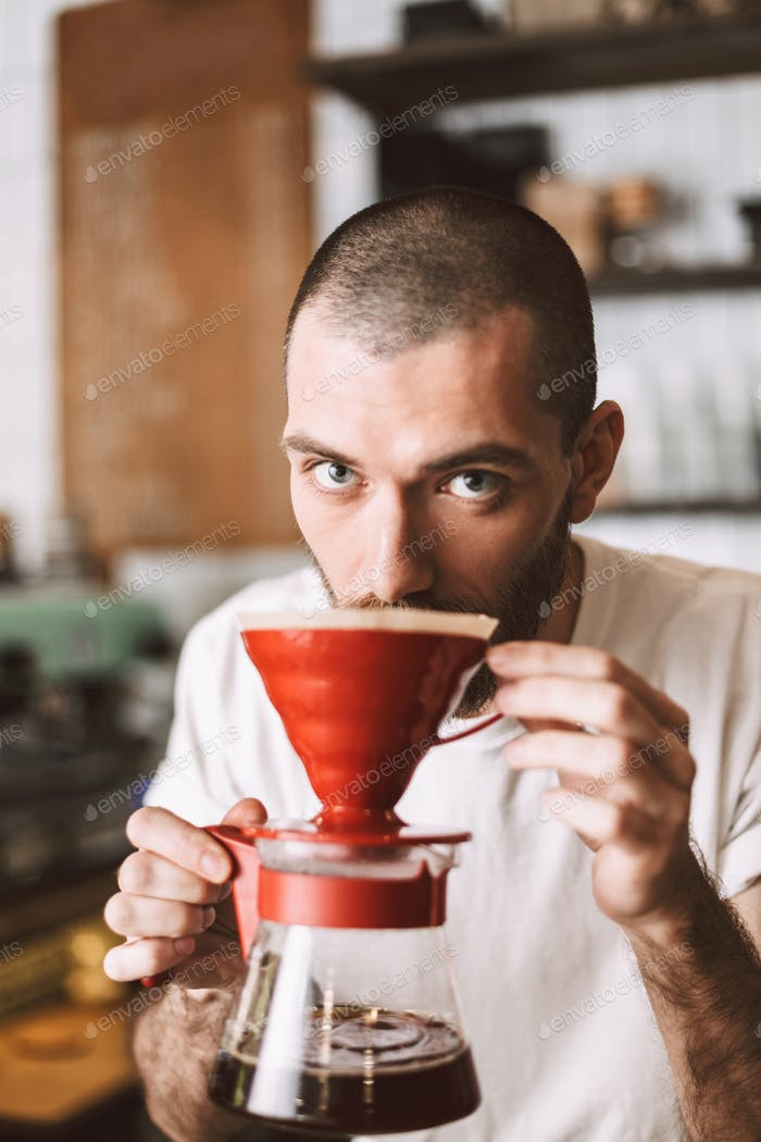 Young barista at bar counter smelling pour over coffee dreamily looking in camera