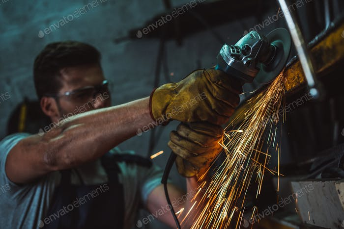 mechanic in goggles working with circular saw in garage