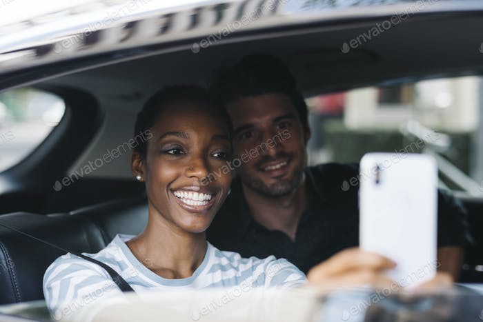 Couple taking selfie in a car