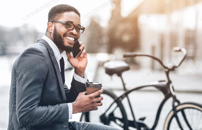 African-american businessman talking on phone sitting outdoors