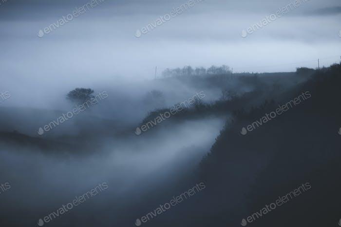 dark fantasy landscape with fog and hills
