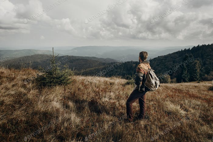 hipster traveler with backpack posing on top of mountains