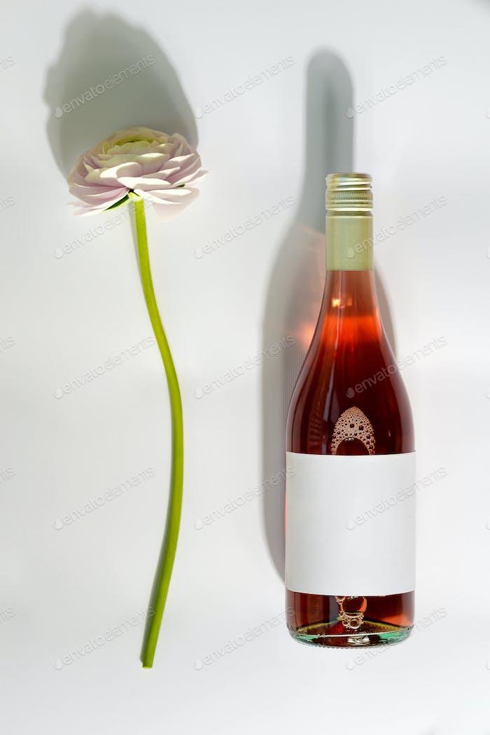 Mock-up Flasche trockener Rosenwein mit natürlichen weißen Blüten