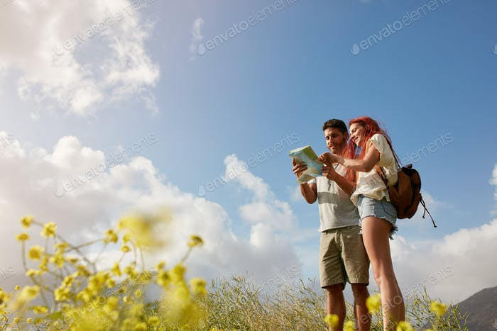 Young couple reading map on country walk