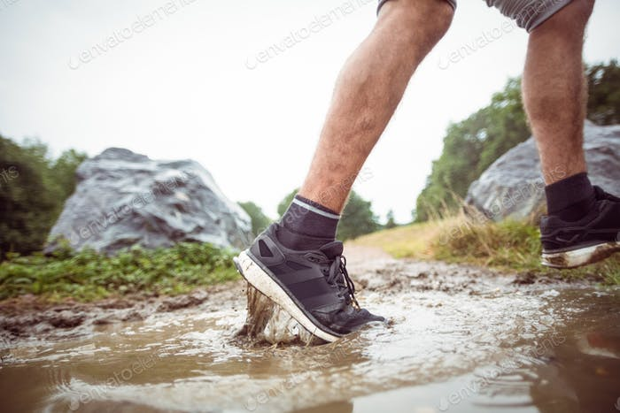 Man walking in muddy puddles in the countryside