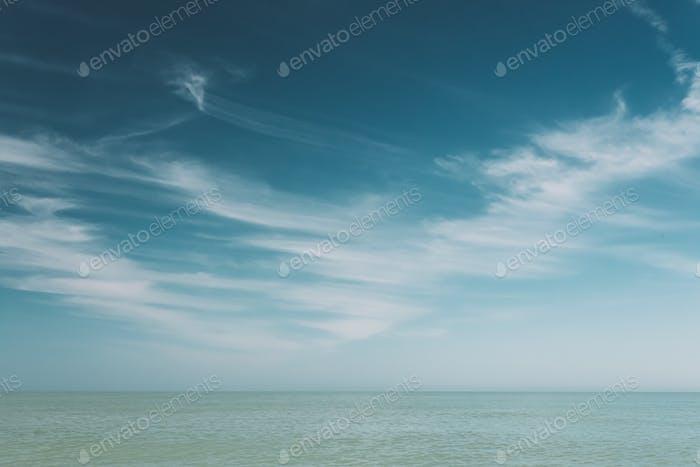 Blauer Himmel über dem ruhigen Wasser des Meeres Ozean. Natürlicher Hintergrund mit sanften blauen Farben