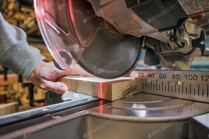 Caucasian man carpenter worker working driving circular saw to cut boards