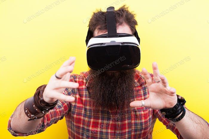 Lange bärtige Hipster Mann mit einem Virtual Reality VR Headset ein