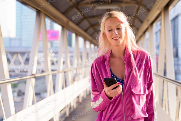Happy young beautiful blonde woman using at the footbridge