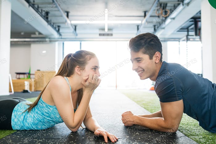 Young fit couple in gym lying on the floor, resting.
