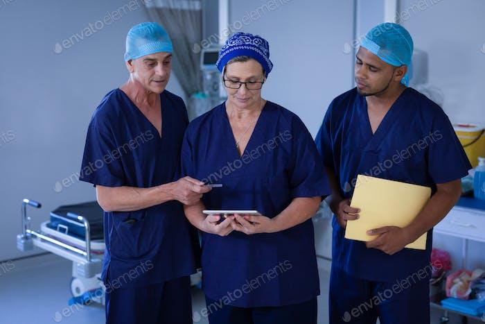 Vorderansicht der multiethnischen Chirurgen diskutieren über digitale Tablette im Krankenhaus