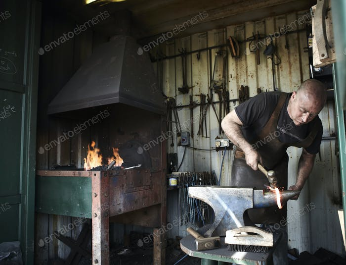 Blacksmith shaping a hot piece of iron on an anvil in a traditional forge with an open fire.
