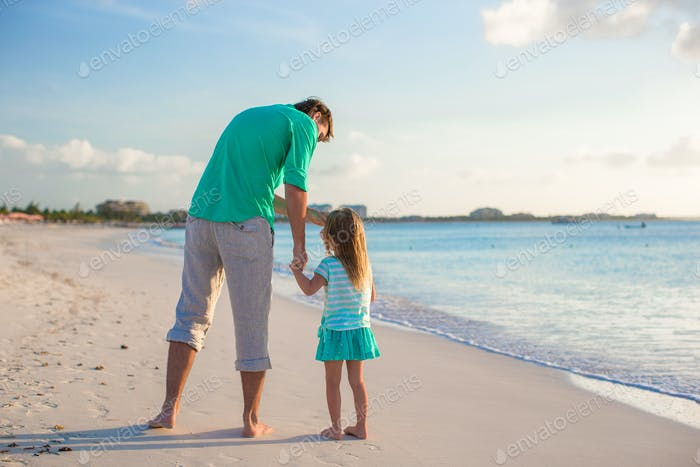 Happy father and his cute little daughter at beach