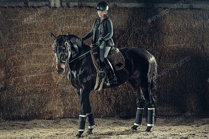 Bild von glücklichen Weibchen sitzt auf reinrassigen Pferd