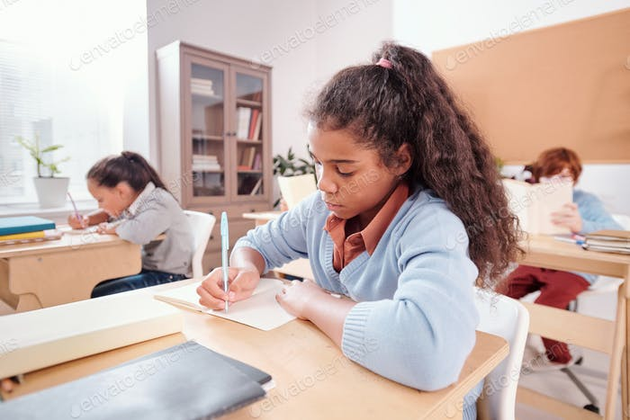 Serious mixed-race schoolgirl making notes or wtiting essay in copybook