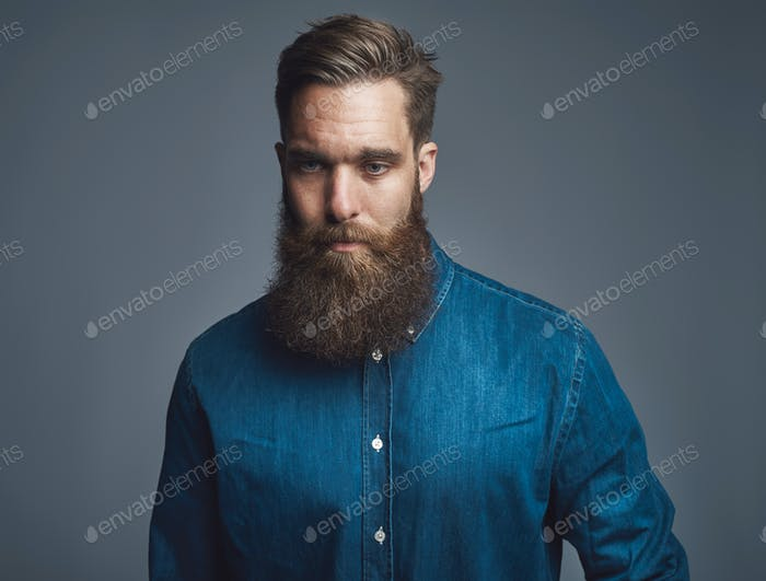 Pensive young bearded man standing against a gray background