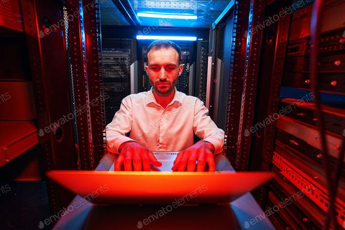 Data center operations specialist typing on laptop keyboard