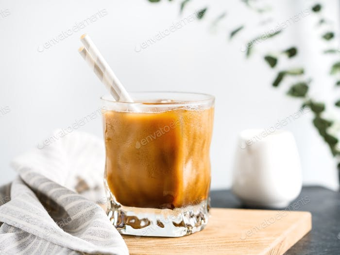Refreshing iced latte coffee in a glass with straws in a modern kitchen.