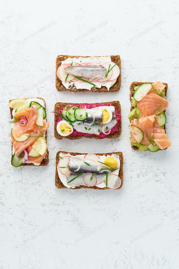 Savory fish smorrebrod, set of five traditional Danish sandwiches. Black rye bread