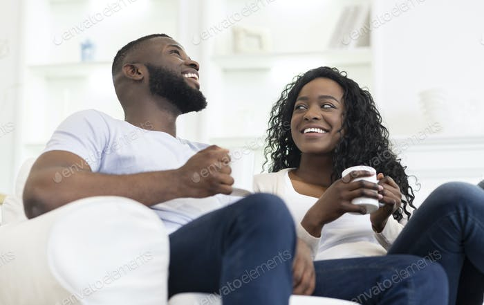 Cheerful black couple relaxing with cup of coffee at home