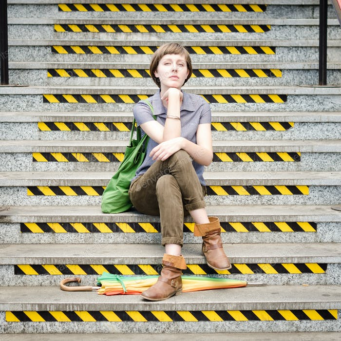 young beautiful hipster woman sitting on the stairs