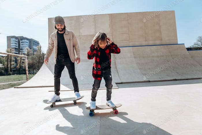 Father and his little son dressed in the casual clothes ride skateboards in a skate park with slides