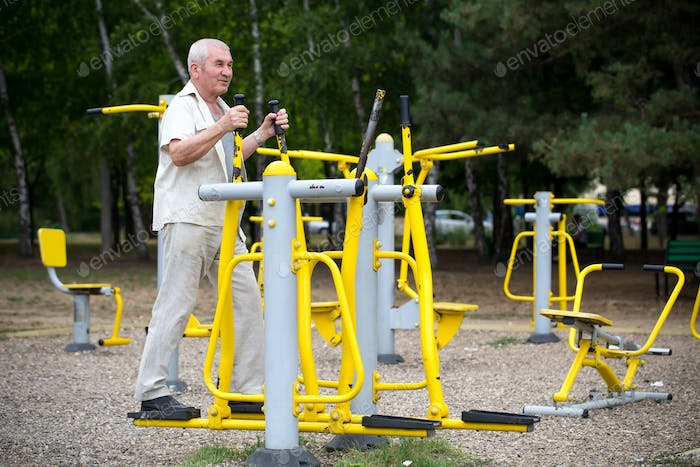Old man making exercises on outdoor gym.