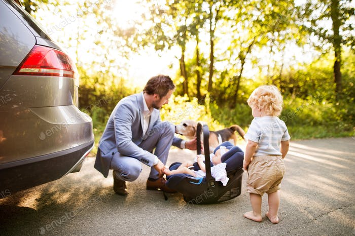 Young father with baby and toddler by the car.