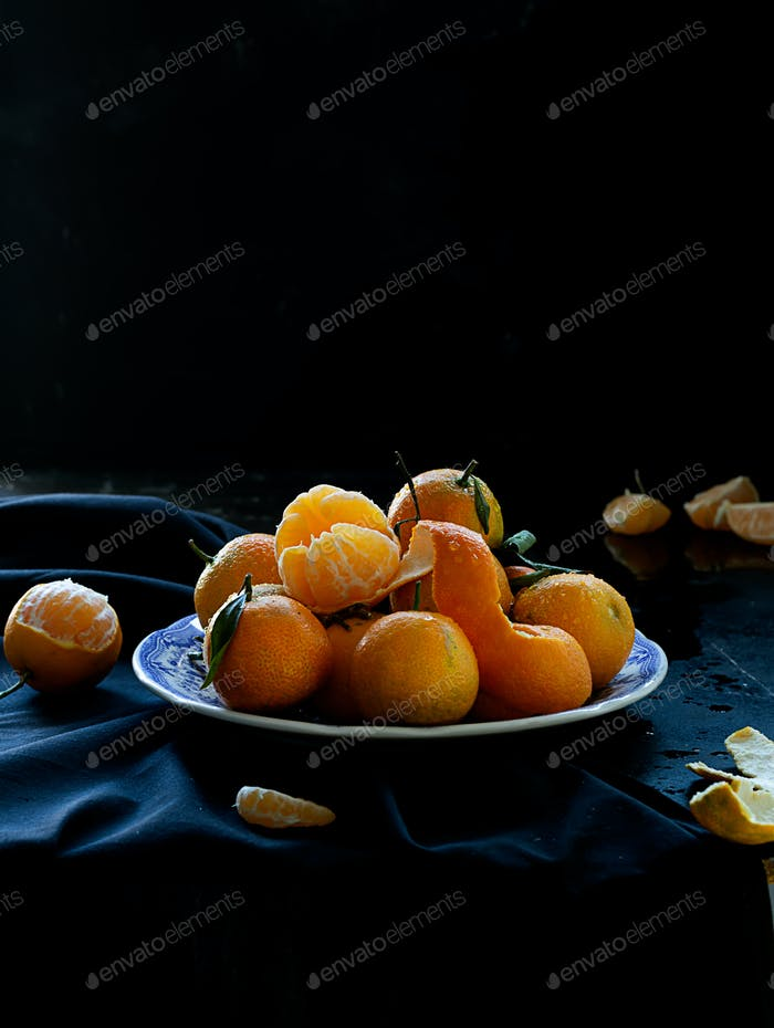 Fresh spanish mandarin oranges fruit with leaves on rustic table, dark and moody style