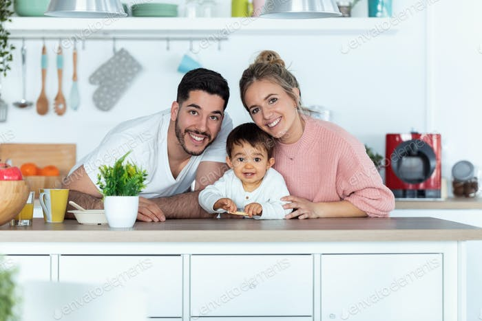 Hübsche junge Eltern und sie Baby Sohn schauen Kamera in der Küche zu Hause.