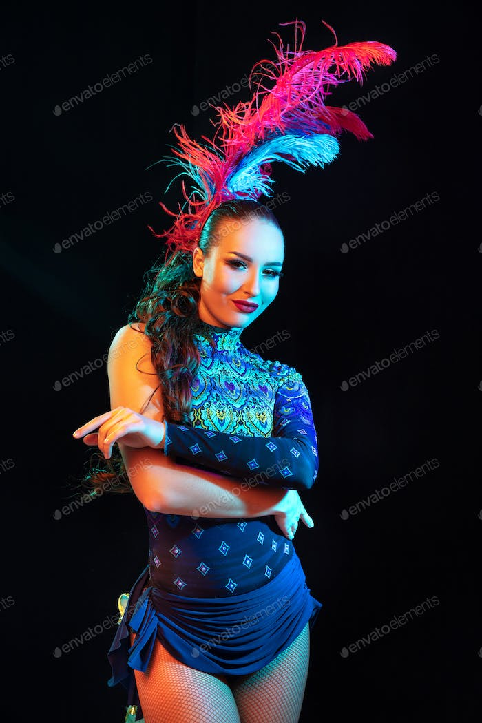 Beautiful young woman in carnival and masquerade costume in colorful neon lights on black background