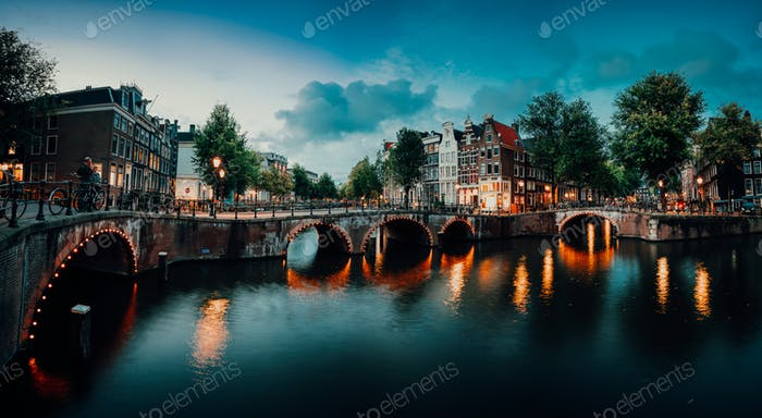 Evening twilight panorama of Amterdam cityscape with canal, bridge and medieval houses in the