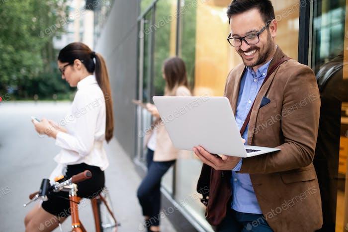 Glückliche Geschäftskollegen reden und spazieren in der Stadt im Freien