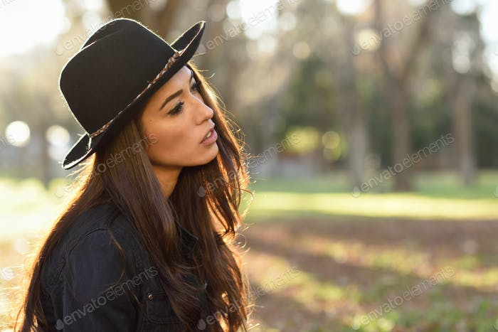 Thoughtful woman sitting alone outdoors wearing hat
