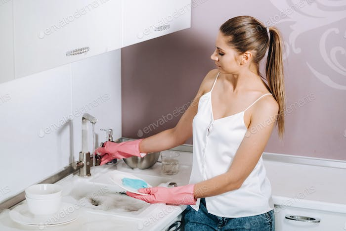 housewife girl in pink gloves washes dishes by hand in the sink with detergent. The girl cleans the