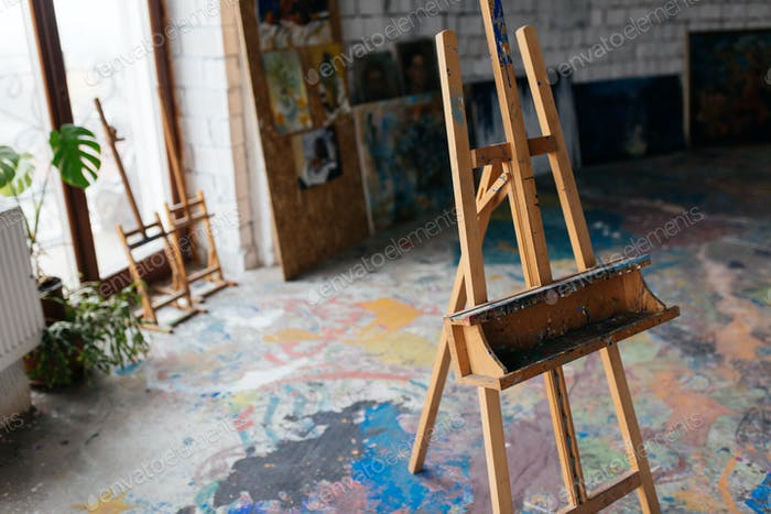 Close up photo of classic wood easel in modern art workshop with
