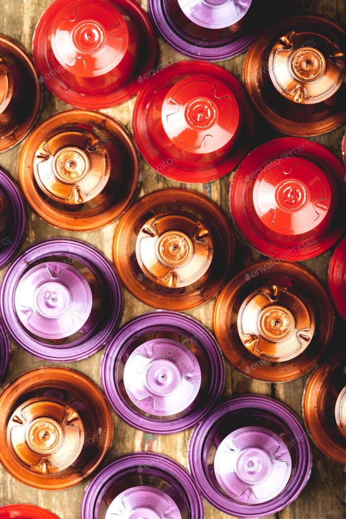 Espresso Kaffeekapseln oder Hülsen und Kaffeebohnen auf rustikalem Holzhintergrund