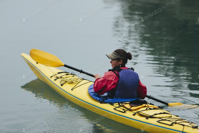 Female sea kayaker in red jacket and life vest
