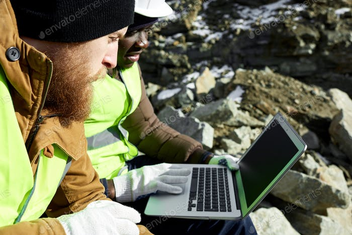 Two Workers Using Laptop on Excavation Site