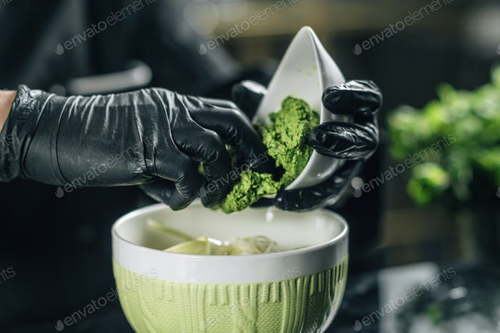 Chef's Hand Preparing Pesto Genovese in Vegetarian Restaurant