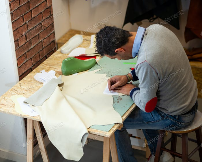 Shoe designer working with leather.