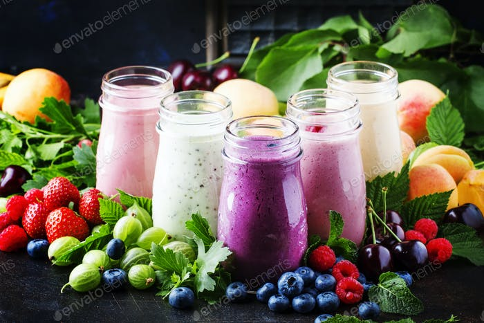 Colorful berry cocktail, smoothies and milkshakes with yogurt, fresh fruit and berries