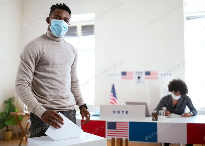 African-american man putting his vote in the ballot box, usa elections and coronavirus