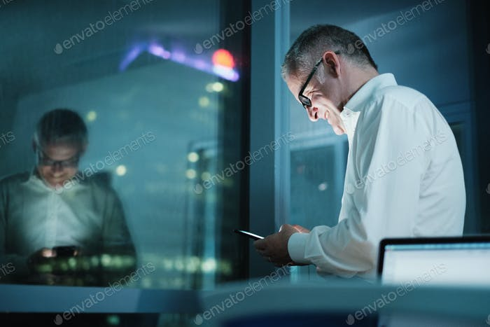 Happy Manager Using Smartphone In Dark Office At Night