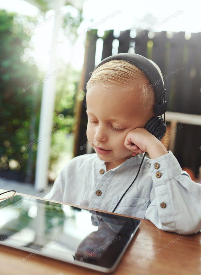 Lächelnder kleiner Junge hört ruhig auf seine Musik
