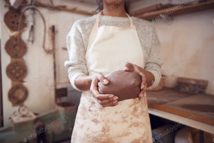 De cerca de la mujer alfarero llevando delantal sosteniendo un trozo de arcilla en el estudio de cerámica